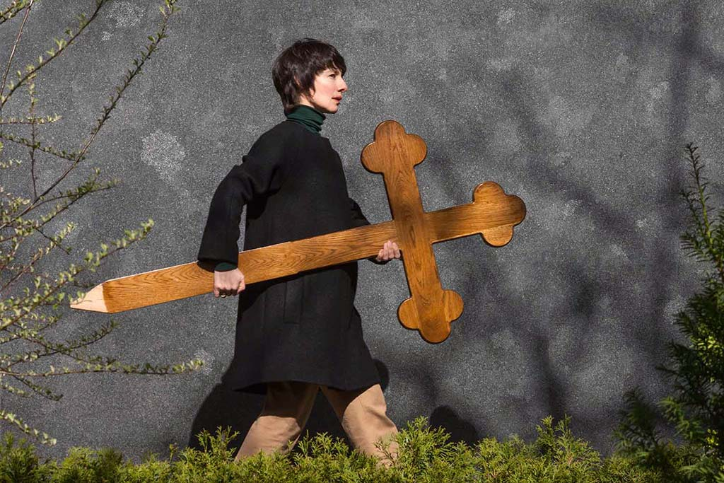 Bestatter Berlin trägt nach Erdbestattungen Grabkreuze aus Holz mit Beschriftung zum Friedhof.