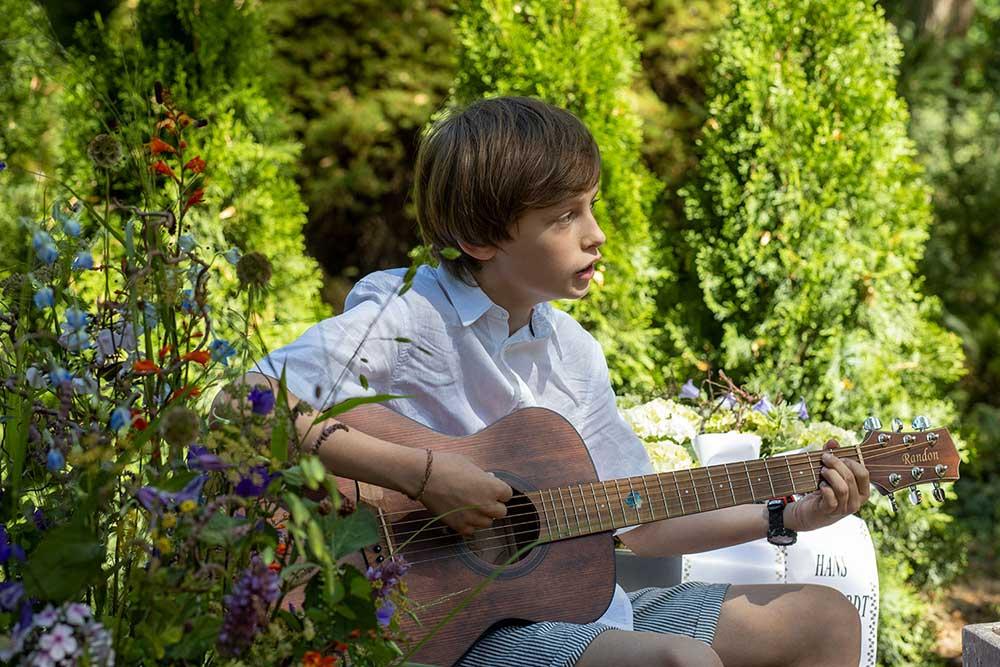 Zur Beerdigung musiziert Enkel Hans auf seiner Gitarre für seinen Opa.