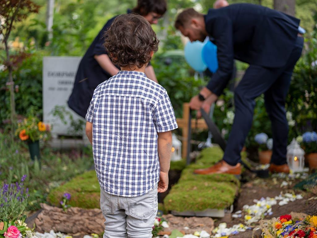Babybestattung auf dem Friedhof Friedenau, der kleine Junge schaut zu als der Sarg seines Bruders ins Grab gelassen wird.